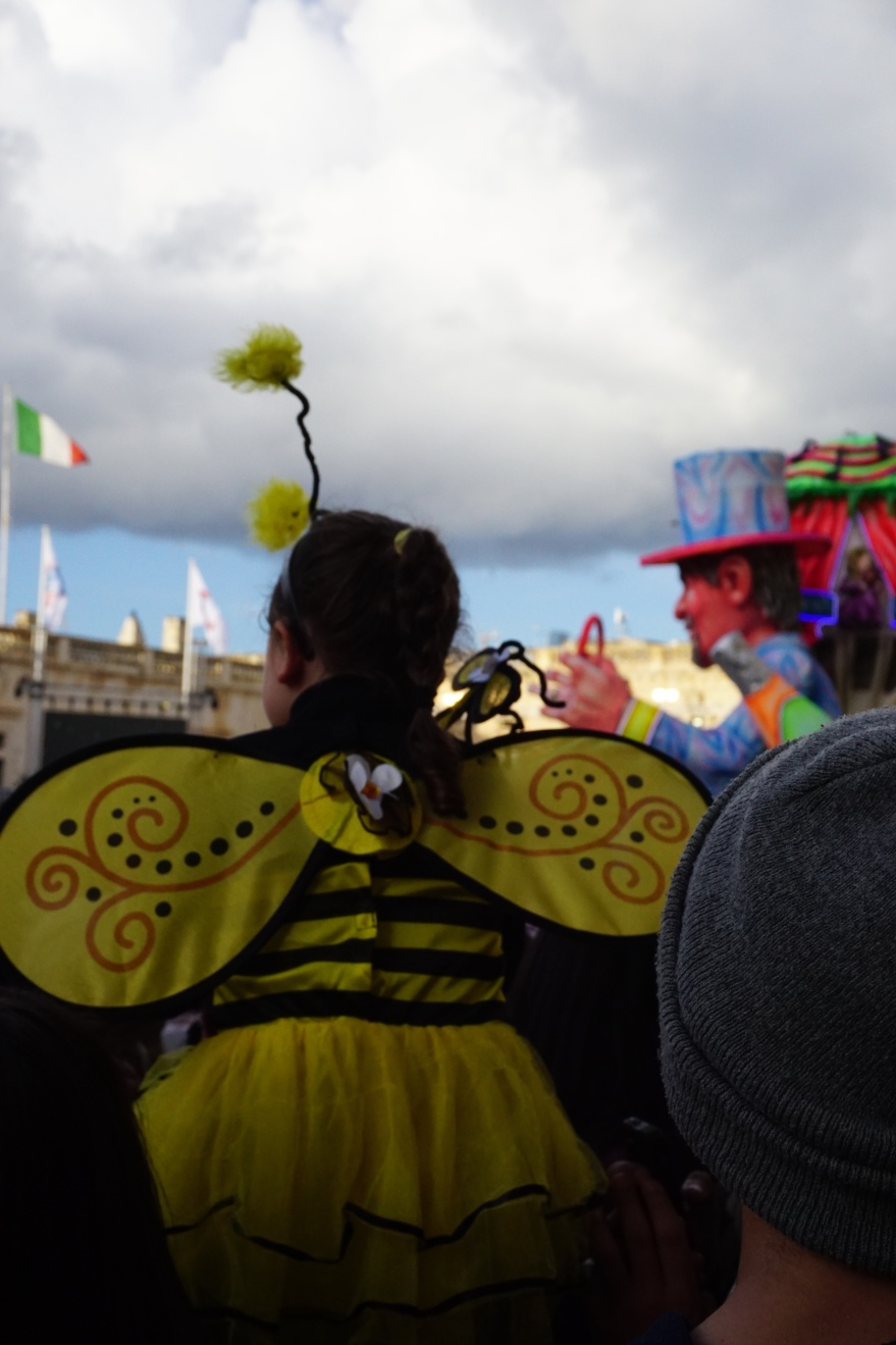 girl in bee costume and floats at the carnival in Malta