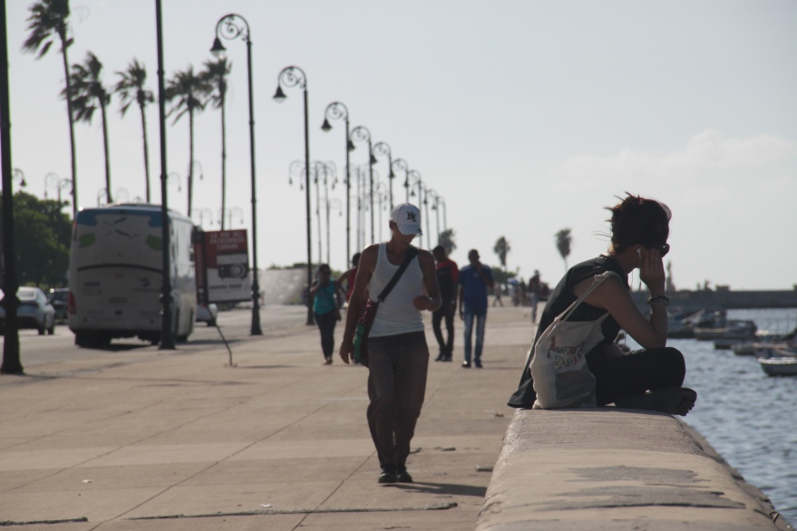 Woman sitting at the Malecón in Havana